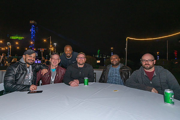 IntelliSurvey employees together at a neon golf course
